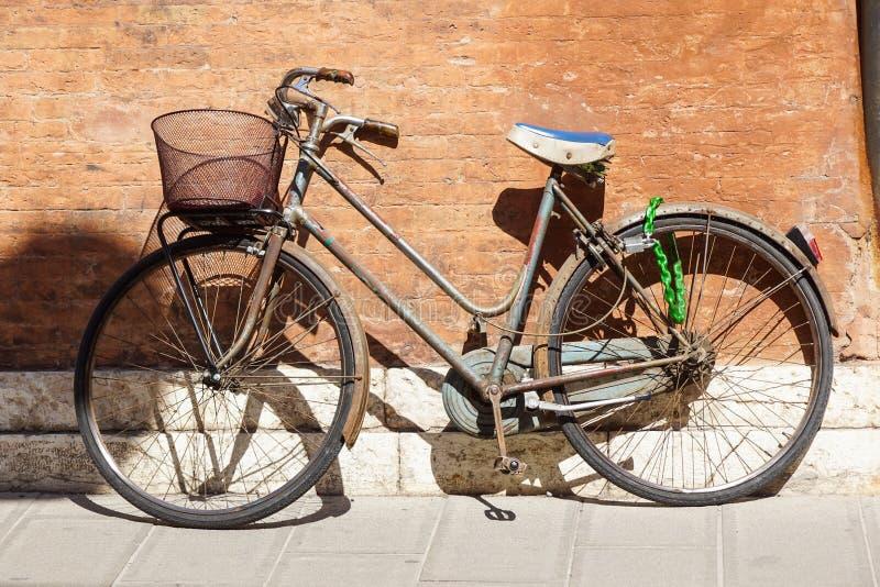 Una vecchia, bicicletta bianca arrugginita con un canestro che pende contro una parete grungy in Italia immagine stock