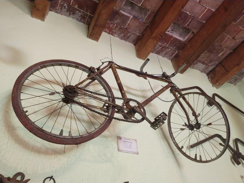Una vecchia bicicletta che appende sulla parete immagini stock libere da diritti