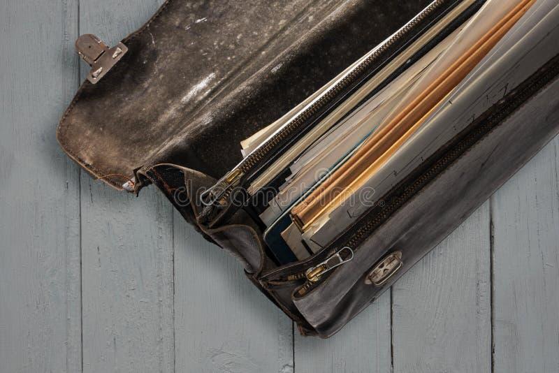 Una vecchia cartella di cuoio nera consumata chiusa con i fermi fotografie stock