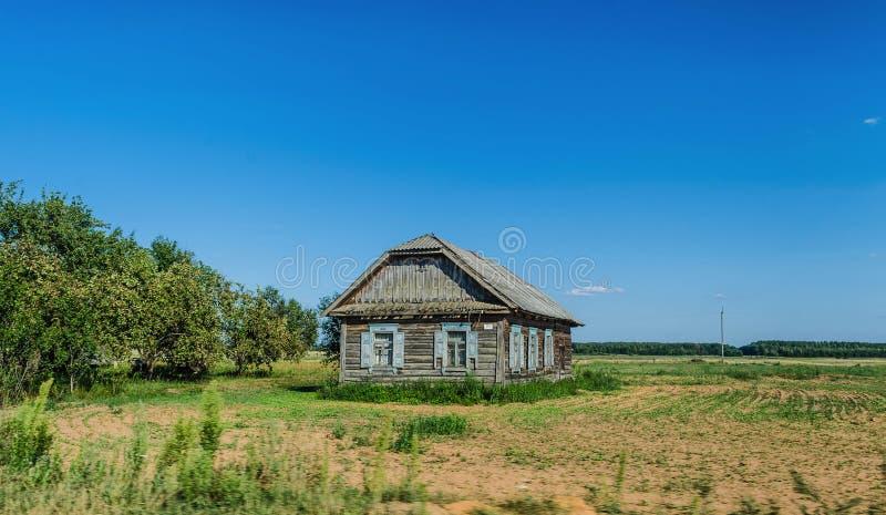 Una vecchia casa abbandonata del villaggio di singola casa dentro fra gli alberi fotografia stock