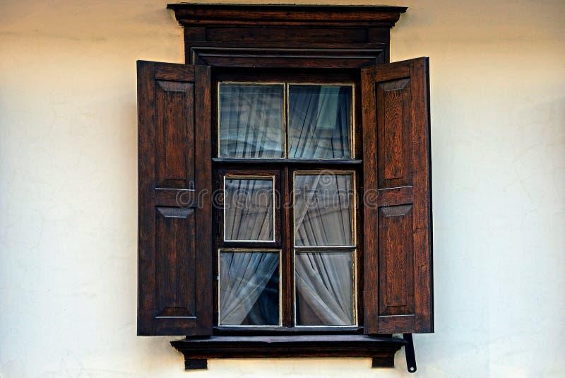 Una vecchia finestra marrone di legno con gli otturatori su una parete grigia fotografia stock libera da diritti