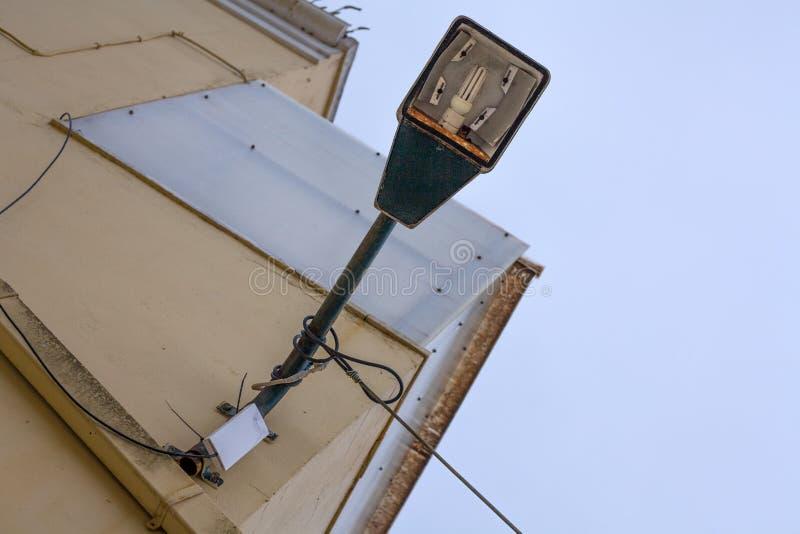 Una vecchia posta arrugginita della lampada a sospensione con i cavi in  Disposto sopra la luce collored la parete fuori della co immagine stock libera da diritti