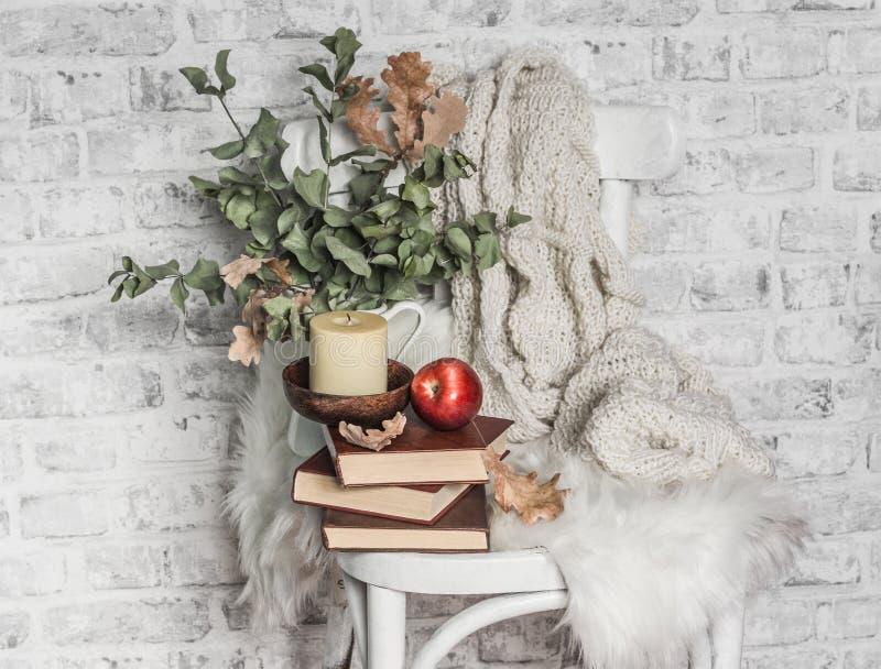 Una vecchia sedia d'epoca, una pila di libri, a maglia, calza, candela, frutta di mele Hobby, divertimento, concetto di confort fotografia stock