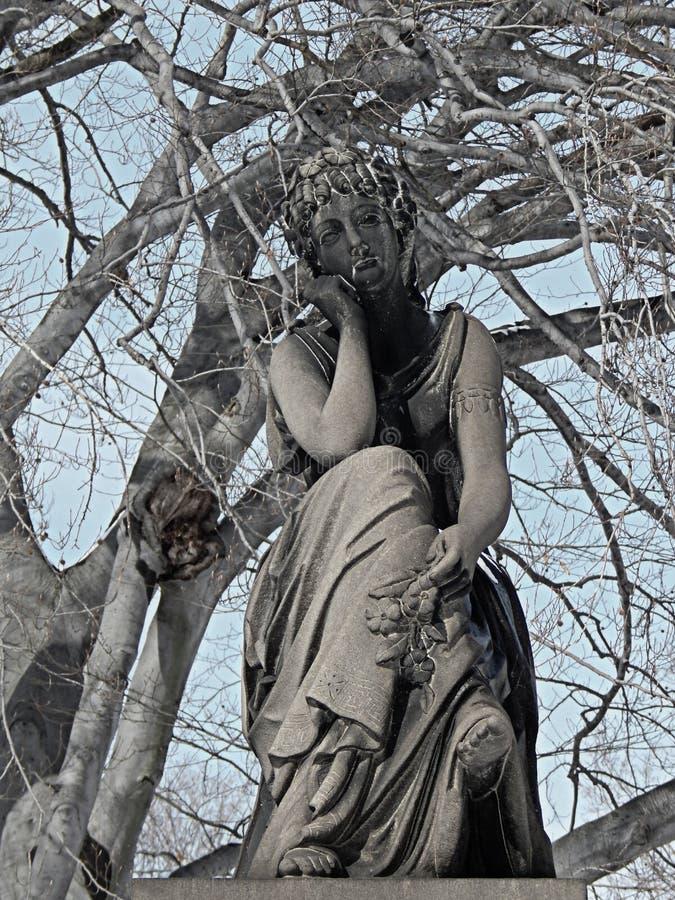 Una vecchia statua del cimitero durante l'inverno immagini stock
