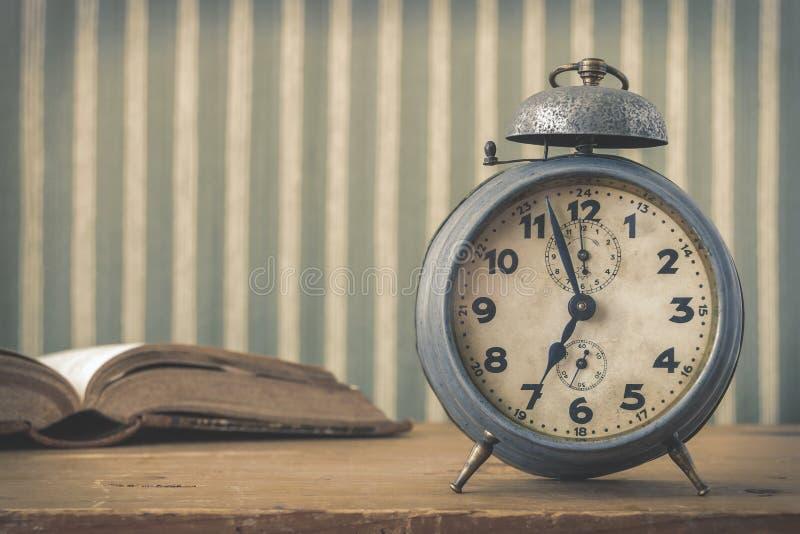 Una vecchia sveglia e un libro aperto fotografia stock libera da diritti