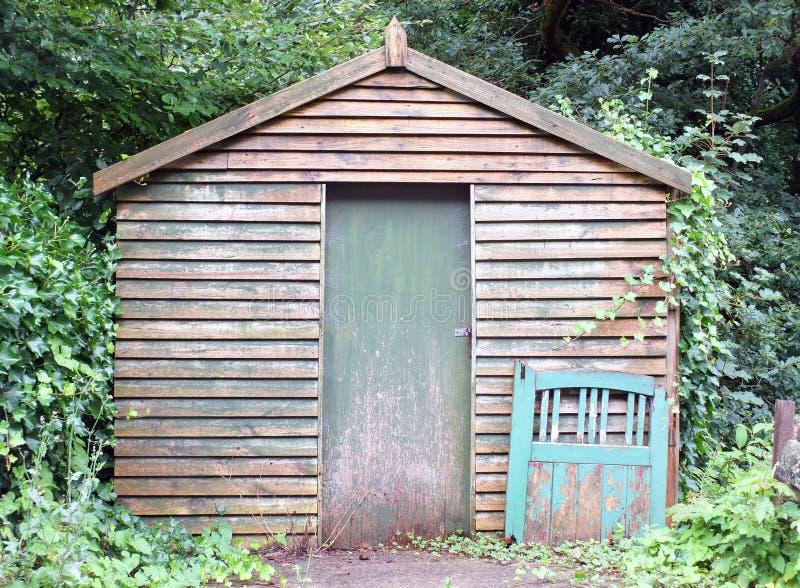Una vecchia tettoia di legno con una porta dipinta verde e portone scartato che si appoggia la parete circondata dagli alberi e d fotografie stock libere da diritti