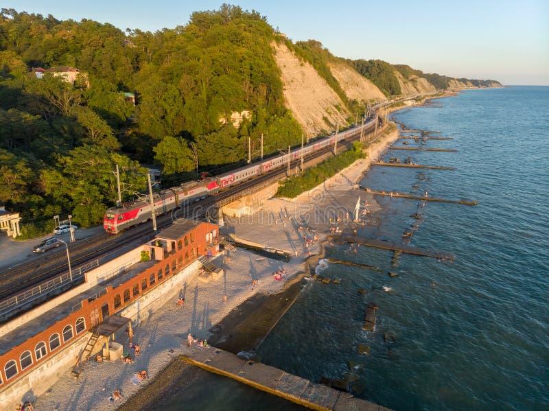 Una veduta panoramica della stazione ferroviaria di Gizel-Dere e del treno di passaggio lungo la costa di Mar Nero su una sera ca fotografia stock