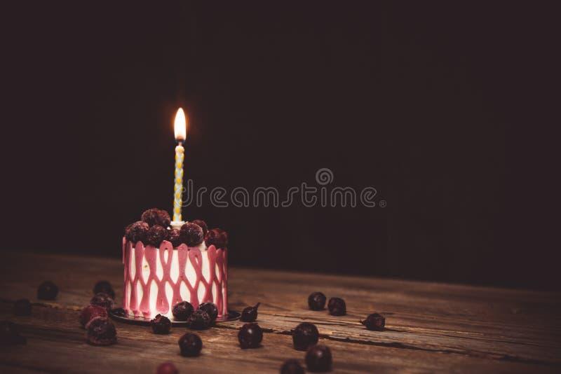 Una vela ardiendo en una torta festiva de la torta con las frutas de la cereza en una tabla de madera r?stica en un fondo oscuro  imagen de archivo