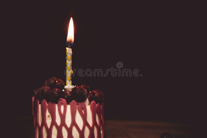 Una vela ardiendo en una torta festiva de la torta con las frutas de la cereza en una tabla de madera r?stica en un fondo oscuro  foto de archivo