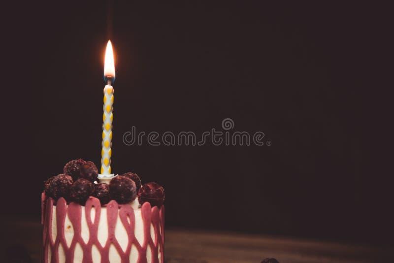Una vela ardiendo en una torta festiva de la torta con las frutas de la cereza en una tabla de madera r?stica en un fondo oscuro  imágenes de archivo libres de regalías