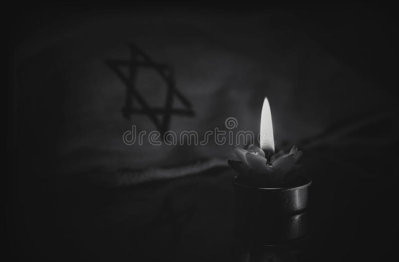 Una vela ardiente al lado de la estrella de David imágenes de archivo libres de regalías
