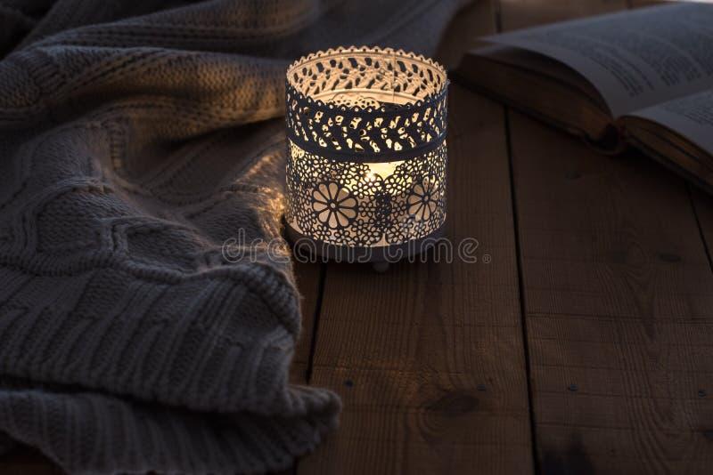 Una vela ardiente, un suéter hecho punto y un libro abierto en una tabla de madera fotografía de archivo libre de regalías