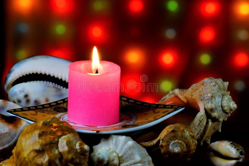 Una vela brillante en un soporte hecho de quemaduras de las cáscaras del mar en el fondo de las luces de la Navidad festiva y del foto de archivo