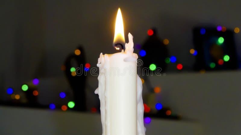 Una vela de la Navidad blanca con las luces borrosas imagenes de archivo