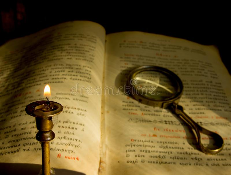Una vela de muerte y un libro de oración viejo con una lupa fotografía de archivo libre de regalías