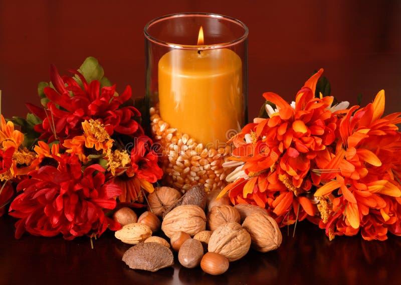 Una vela en una configuración del otoño foto de archivo