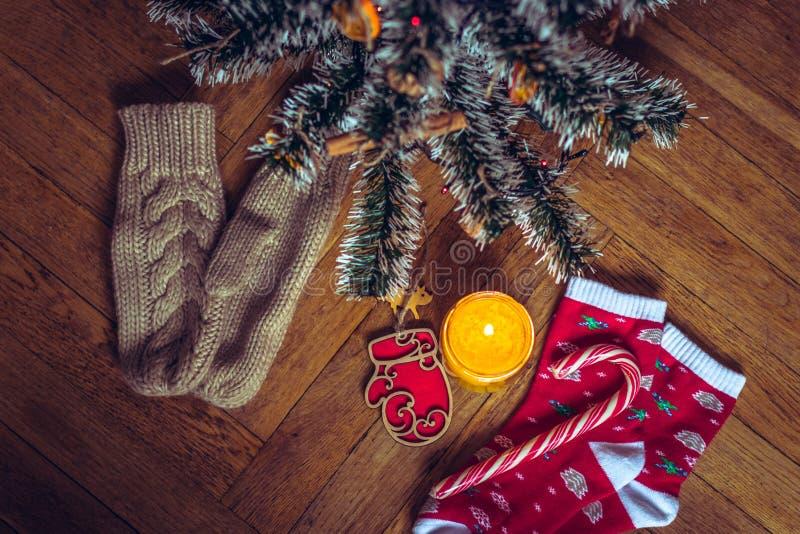Una vela está quemando debajo del árbol de navidad, cerca es galletas, caramelo, calcetines de las lanas y manoplas fotografía de archivo libre de regalías
