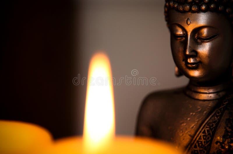 Una vela y una estatua de Buda imagen de archivo