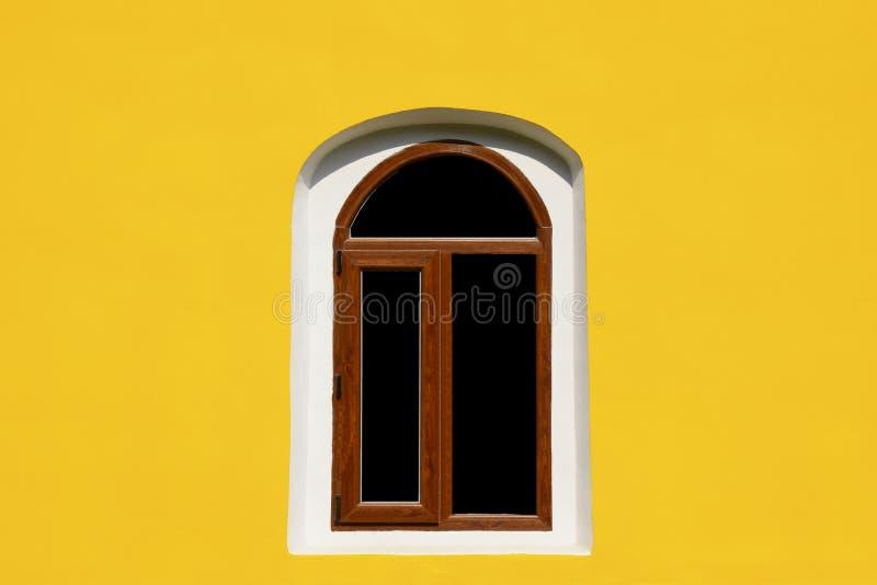 Una ventana del arco en la pared amarilla imagen de archivo