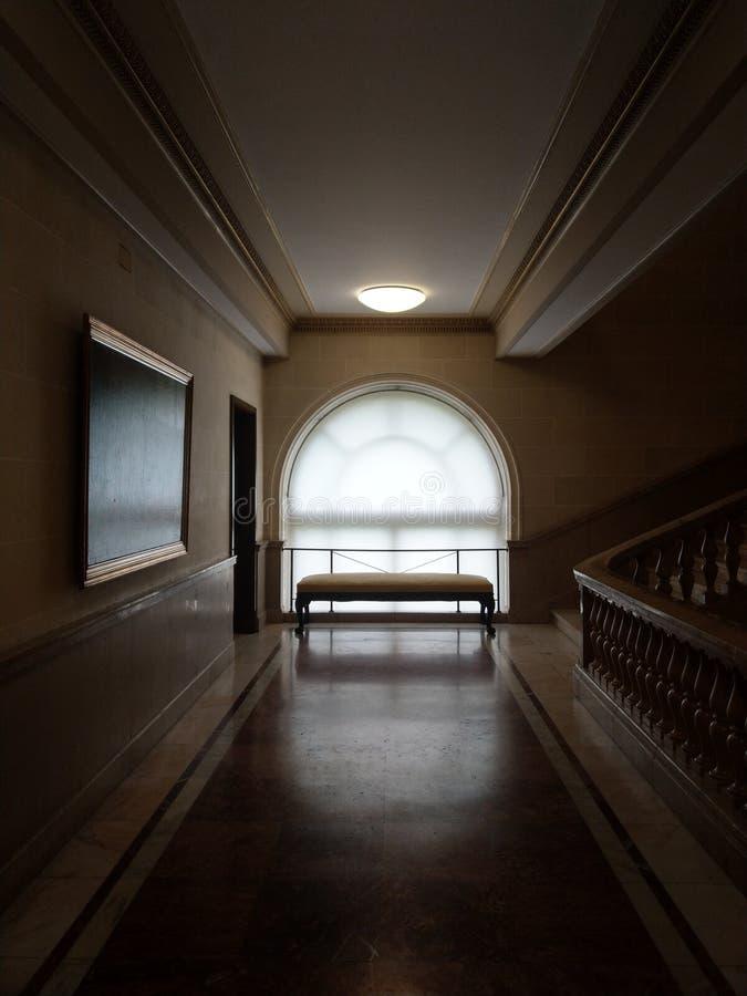Una ventana redondeada con un banco en el final de un vestíbulo del starcase imágenes de archivo libres de regalías