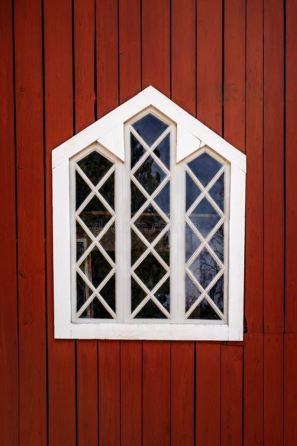 Una ventana tradicional decorativa blanca con el marco de madera en una pared roja del granero foto de archivo