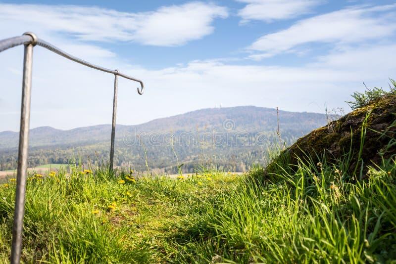 Una verja en un prado, perspectiva profunda, vista de montañas imagen de archivo