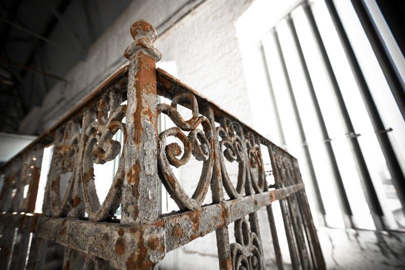 Una verja oxidada vieja del labrado-hierro foto de archivo libre de regalías