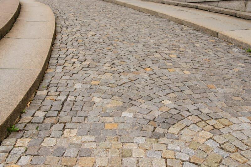 Una via pavimentata con un bordo e un in salita intenso fotografia stock