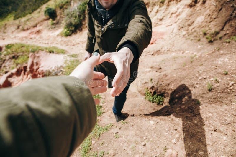 Una viandante dà una mano ad un'altra persona durante l'escursione in un'area montagnosa fotografie stock