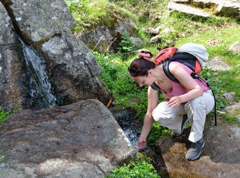 Una viandante vicino al brooklet della montagna immagini stock libere da diritti