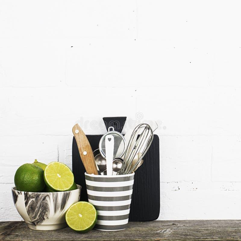 Una vida simple de la cocina aún contra los platos de una pared de ladrillo del blanco de los colores de moda modernos grises, ne imágenes de archivo libres de regalías