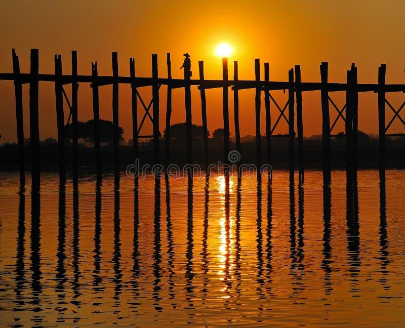 Una vieja figura que cruza el puente de U-Bein en la puesta del sol, Amarapura, Myanmar (Birmania). imágenes de archivo libres de regalías