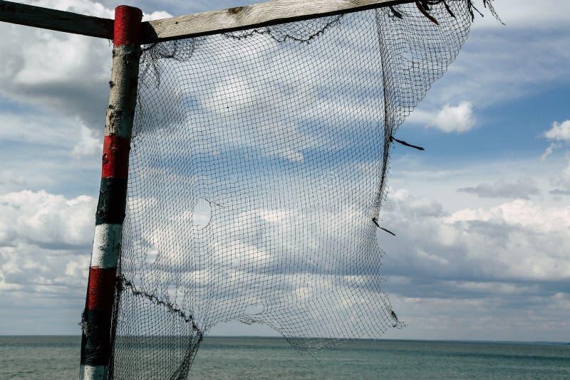 Una vieja red de pesca pesa en un polo y se seca imagenes de archivo