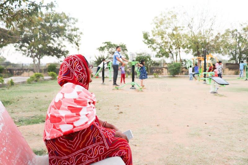 Una vieja señora india que se sienta en el banco y los niños de observación que juegan en un gimnasio abierto en un parque fotos de archivo