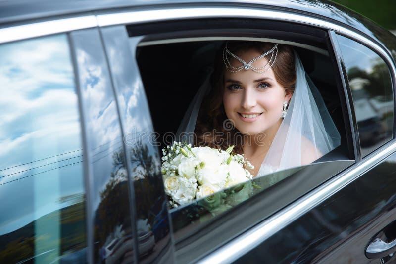 Una visión desde fuera del coche, una novia europea joven se sienta en el asiento trasero de una limusina negra, lleva a cabo una foto de archivo libre de regalías