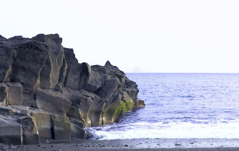 Una visión desde la orilla de rocas volcánicas en el océano de la costa de la isla de Madeira imagen de archivo