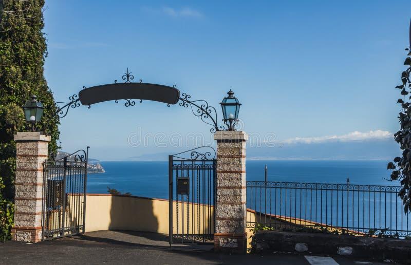 Una visión fantástica desde el acantilado con una puerta hermosa del metal negro y piedras grises con dos luces al mar Mediterrán imágenes de archivo libres de regalías