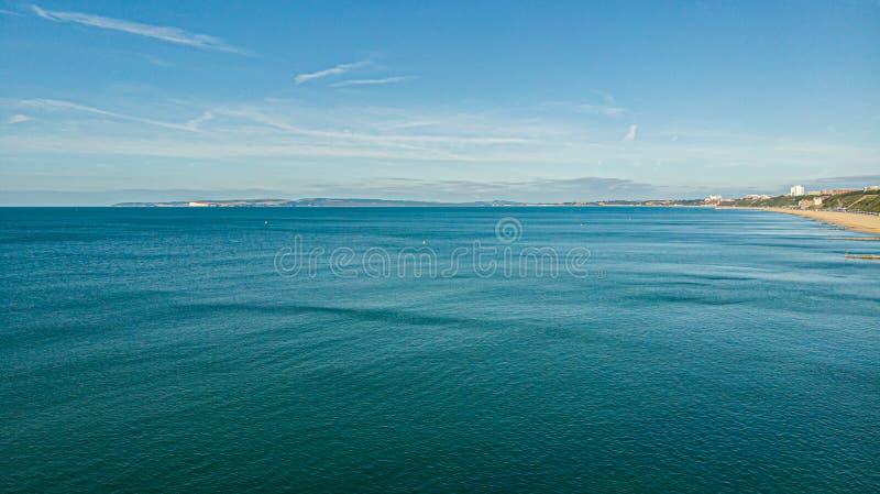 Una vista aérea de un mar cristalino majestuoso del agua azul con un poco de costa costa montañosa en el fondo debajo de un cielo fotografía de archivo libre de regalías