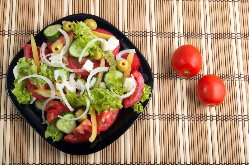 Una vista aerea di una porzione di insalata di verdure su un piatto di blac fotografie stock