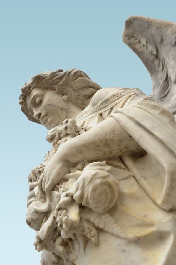 Una vista bassa di angelo di un lookng della statua di angelo giù in modo protettivo fotografie stock