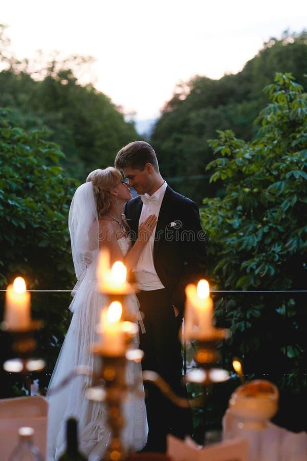 Una vista da dietro le candele brucianti su una condizione delle coppie di nozze fotografie stock libere da diritti