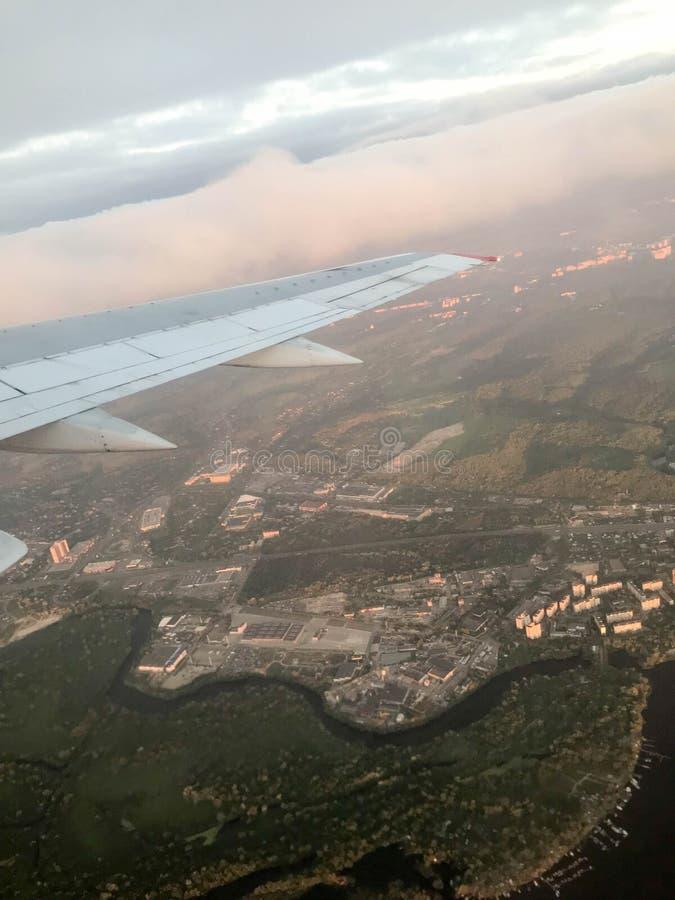Una vista da sopra della città con le costruzioni, le case dall'oblò, le finestre degli aerei sull'ala con i motori, le turbine e immagini stock