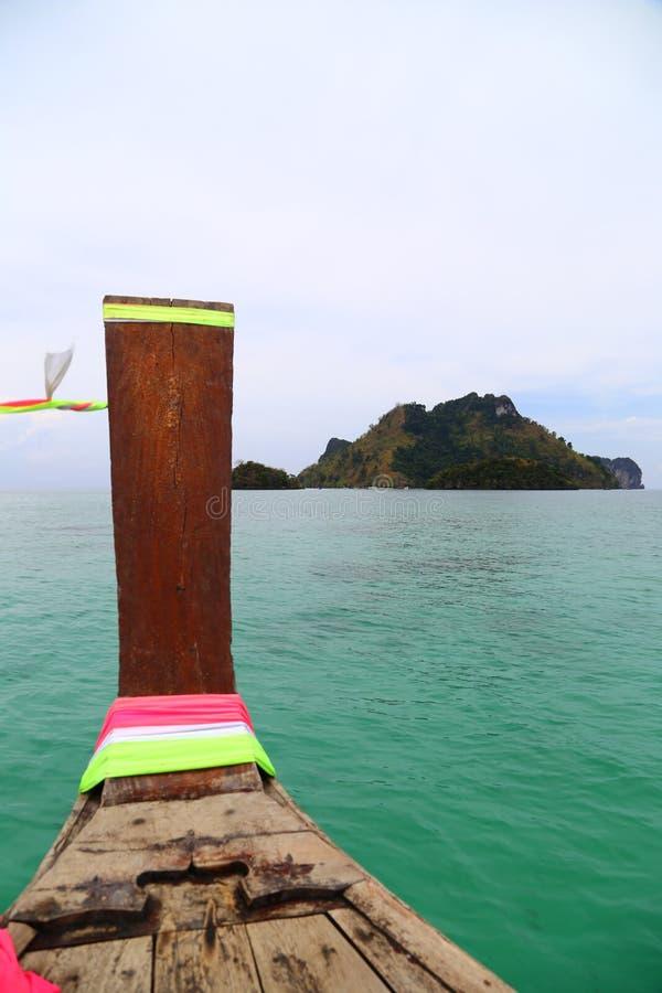 Una vista dal pube di legno con i nastri nel mare con una vista dell'isola immagine stock libera da diritti