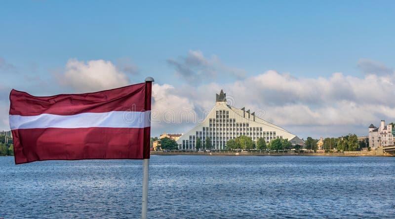 Una vista de la biblioteca nacional letona y de un río con una bandera letona fotos de archivo