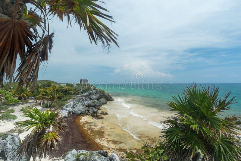 Una vista de la playa y del océano debajo del templo de las ruinas mayas de dios del viento en Tulum imagenes de archivo