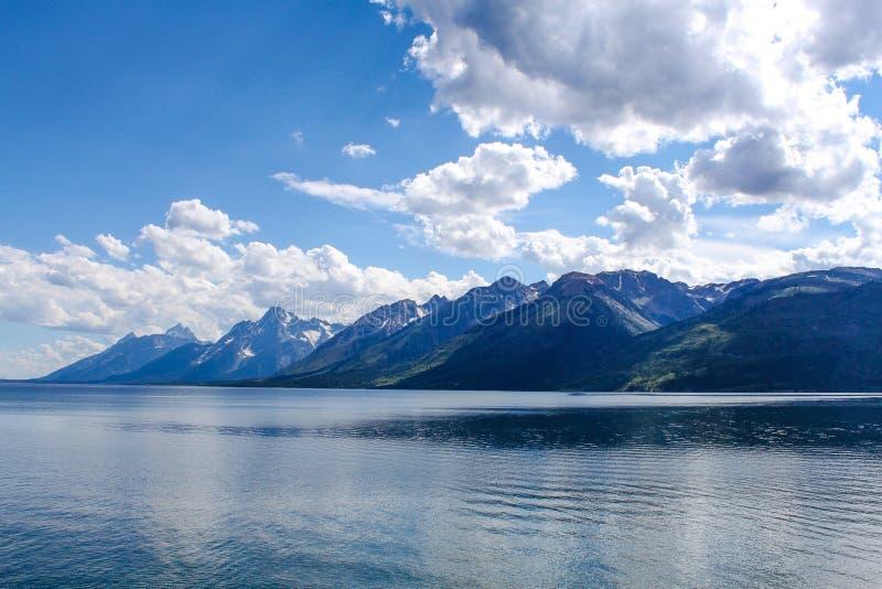 Una vista de las montañas magníficas de Tetons a través del lago imagenes de archivo