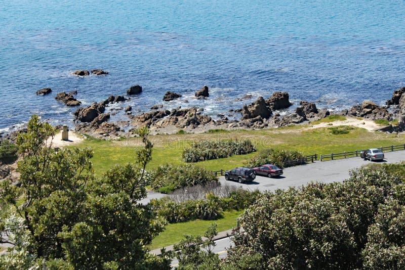 Una vista de las rocas y de la estatua de Moai en el banco de Lyal Bay, Wellington, Nueva Zelanda imágenes de archivo libres de regalías
