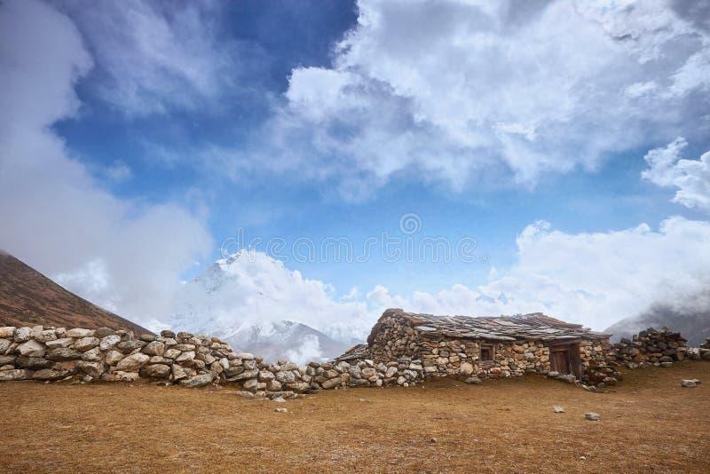 Una vista de los picos con la choza de piedra vieja, viaje del campo bajo de Everest, Nepal de Amphu Gyabjen y de Ama Dablan fotos de archivo
