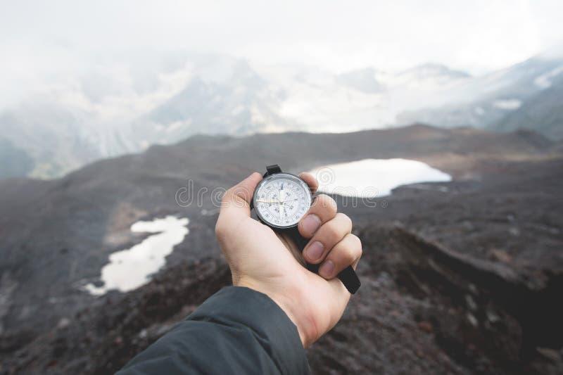 Una vista de primera persona de la mano de un hombre que lleva a cabo un compás magnético contra la perspectiva de las montañas c fotografía de archivo libre de regalías