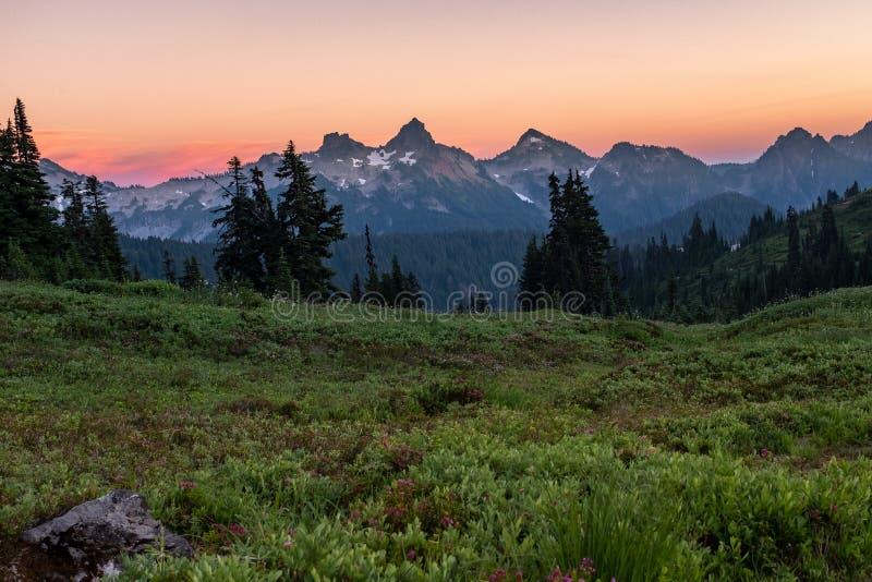 Una vista de una puesta del sol hermosa sobre una gama de montañas de enfrente de un prado con los wildflowers, el cielo es un co imágenes de archivo libres de regalías
